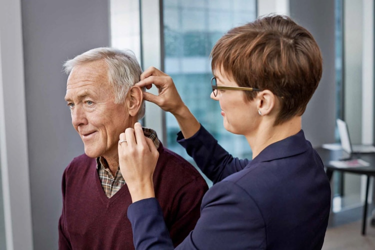 senior man getting fitted for hearing aid